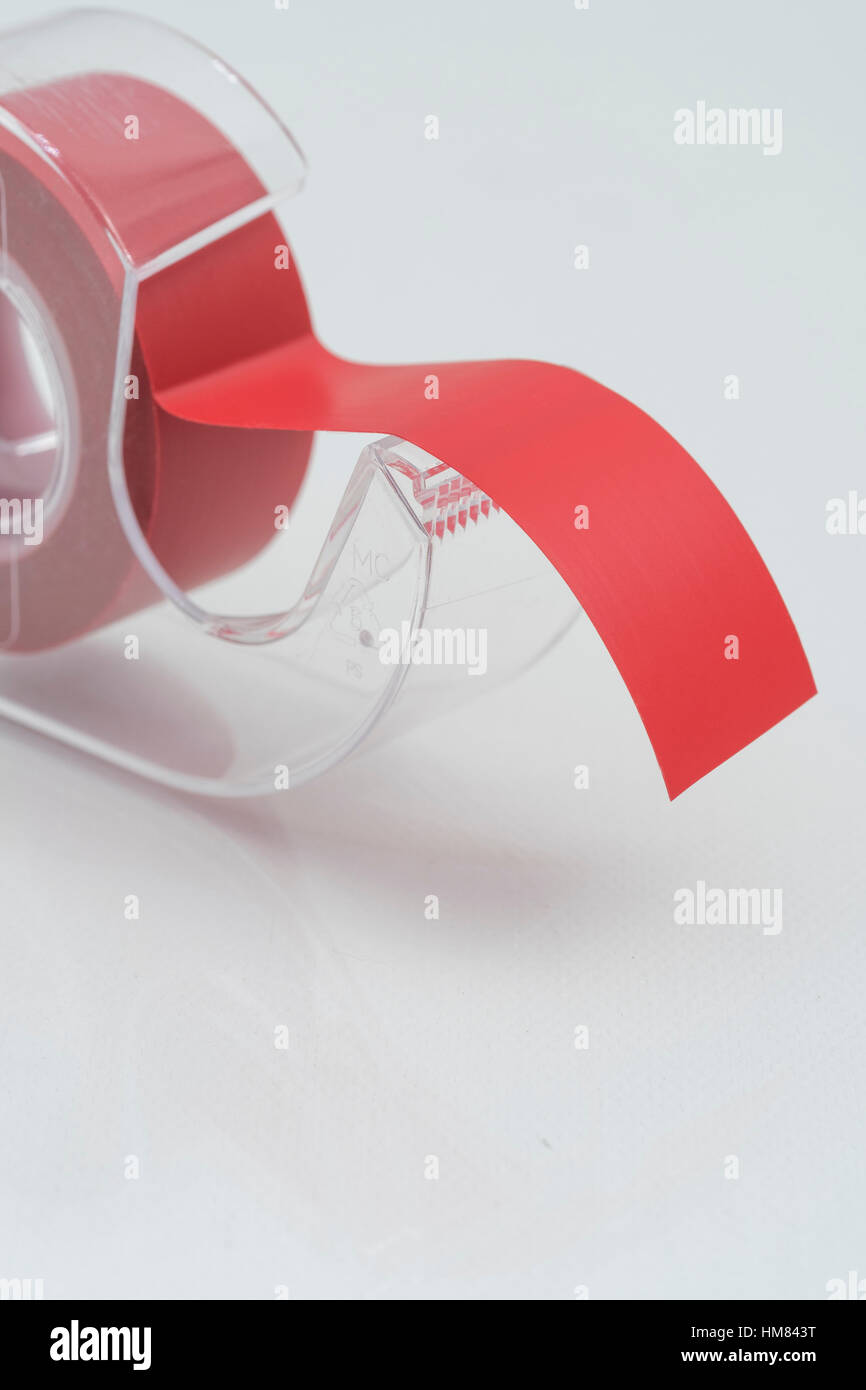 Rullo o nastro rosso in un nastro adesivo dispenser - come metafora visiva per l incubo della burocrazia, burocrazia burocrazia, tagliare il nastro rosso. Foto Stock