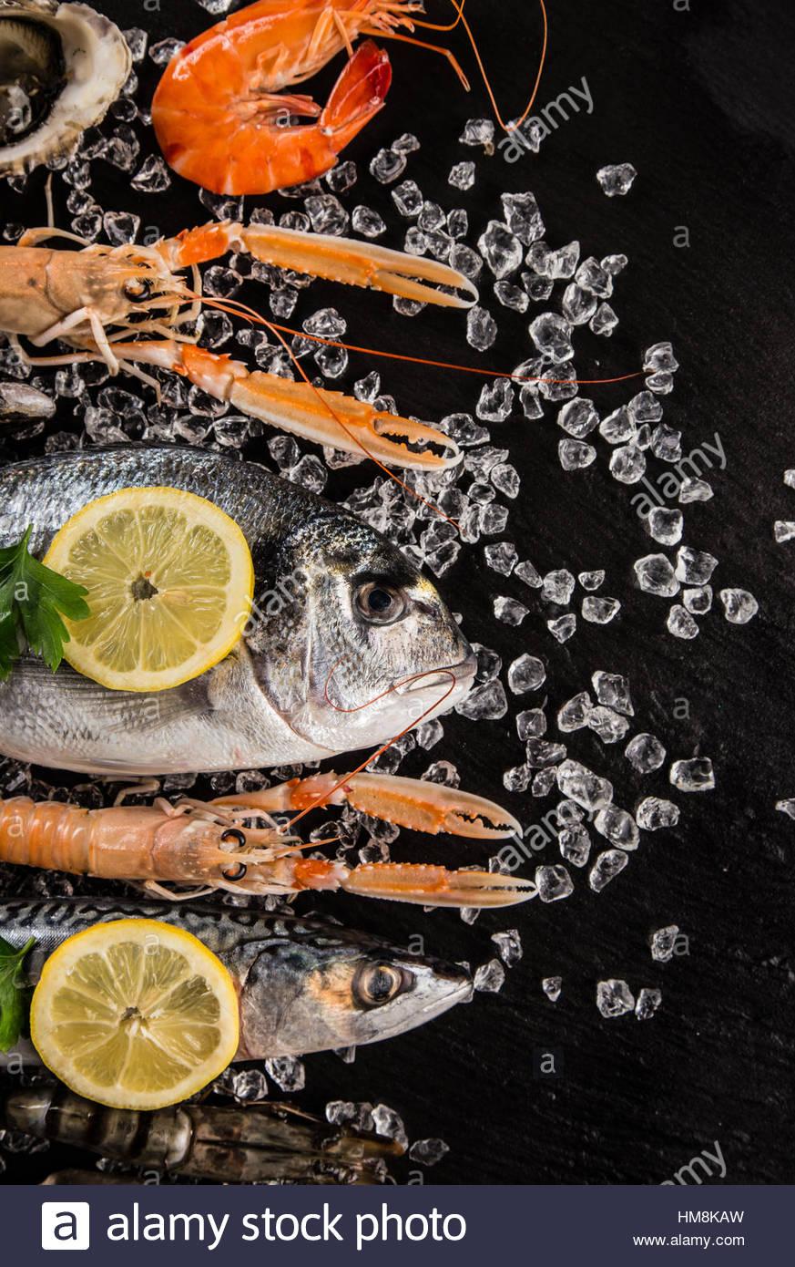 Piatti a base di frutti di mare freschi sulla pietra nera, close-up. Immagini Stock