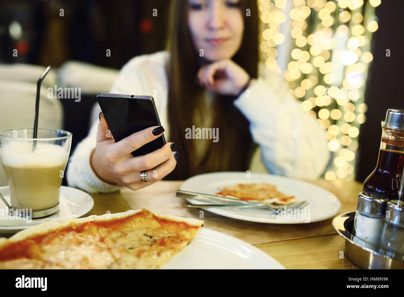 Donna digitando Scrivi messaggio sul telefono intelligente in un moderno cafe'. Immagine ritagliata della giovane Immagini Stock