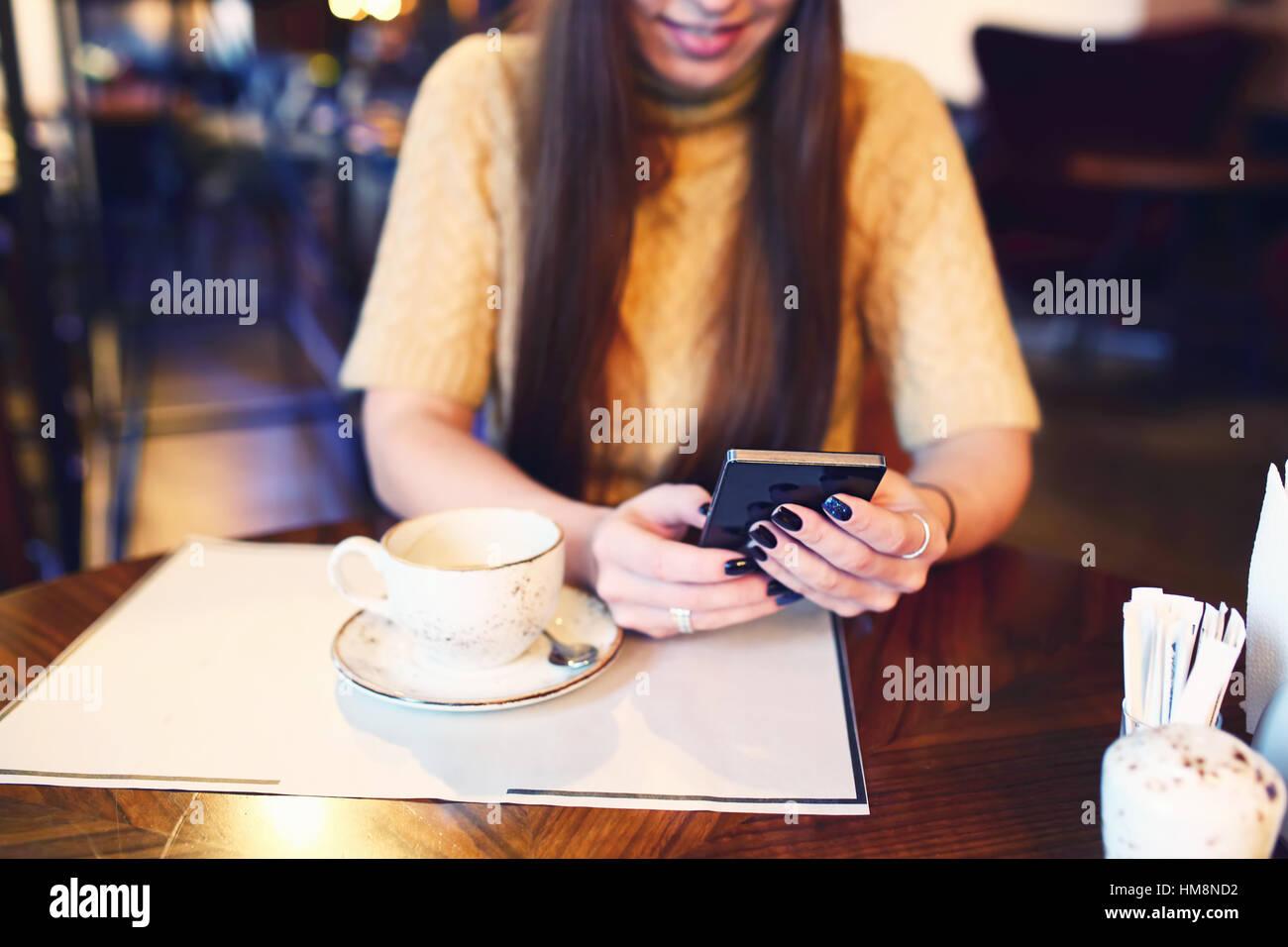 La donna la digitazione di un messaggio di testo sul telefono intelligente in un cafe'. Immagine ritagliata Immagini Stock