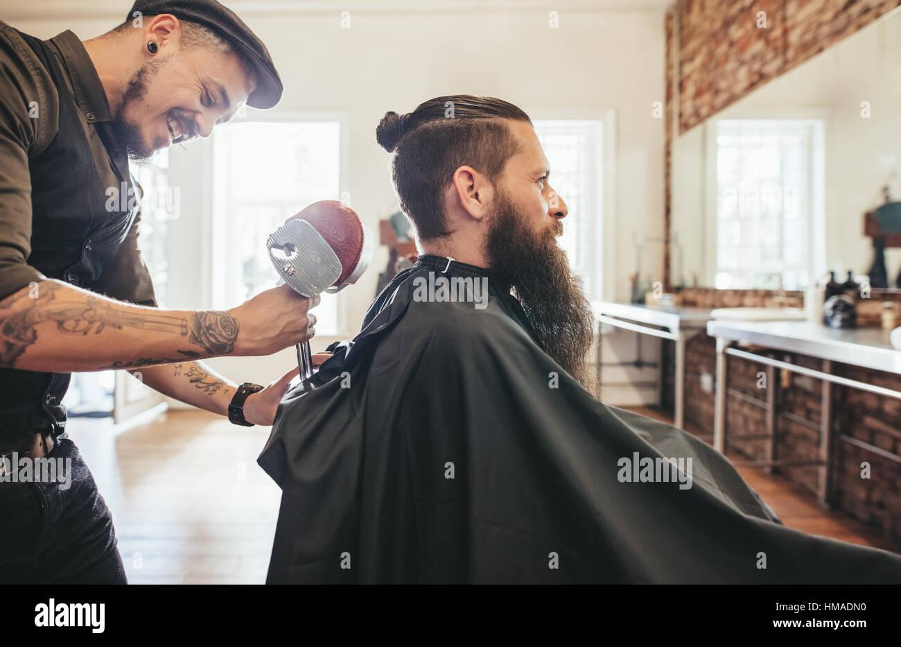 Bel uomo barbuto in un salone cape del barbiere, parrucchiere con regolazione del poggiatesta della sedia. Immagini Stock