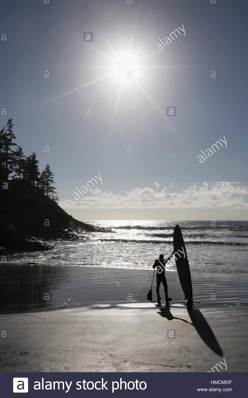 Paddleboarder in piedi con paddleboard di sunny beach Immagini Stock