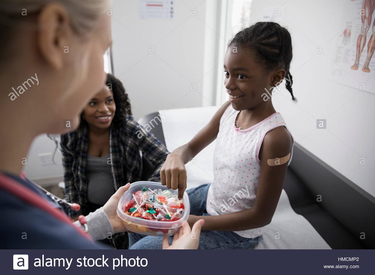 Femmina offerta infermiere paziente ragazza candy in clinica sala esame Immagini Stock