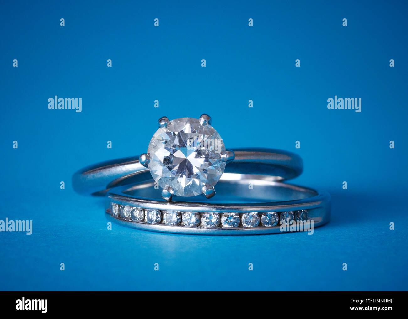 Un diamante solitario anello di fidanzamento impilati su un diamante wedding band contro uno sfondo blu Immagini Stock