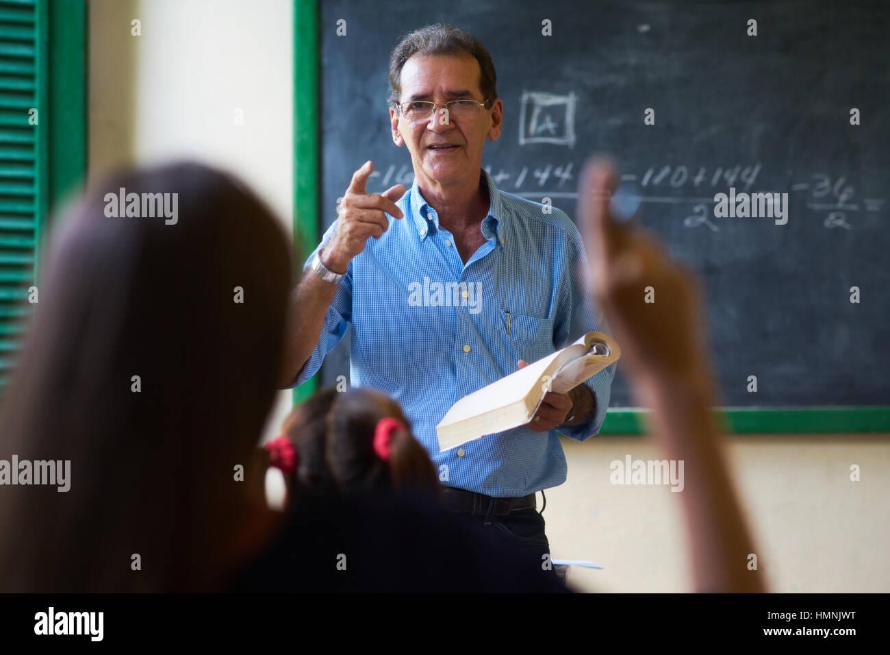 I giovani e l'istruzione. Gruppo di studenti ispanici in classe a scuola durante la lezione. Ragazza alzando Immagini Stock