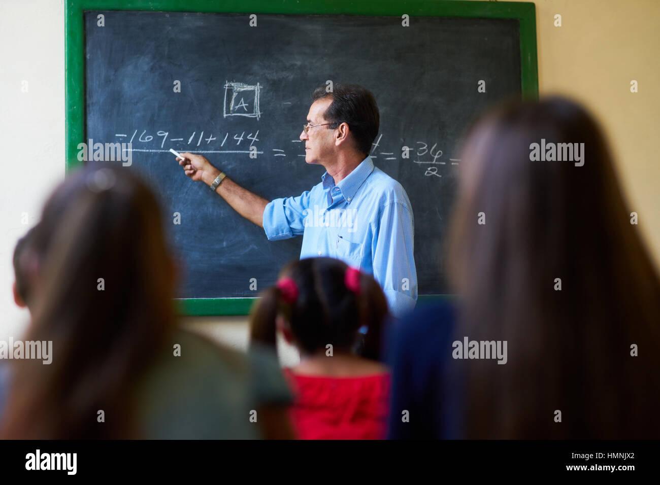 I giovani e l'istruzione. Gruppo di studenti ispanici in classe a scuola durante la lezione. Focus su insegnante Immagini Stock