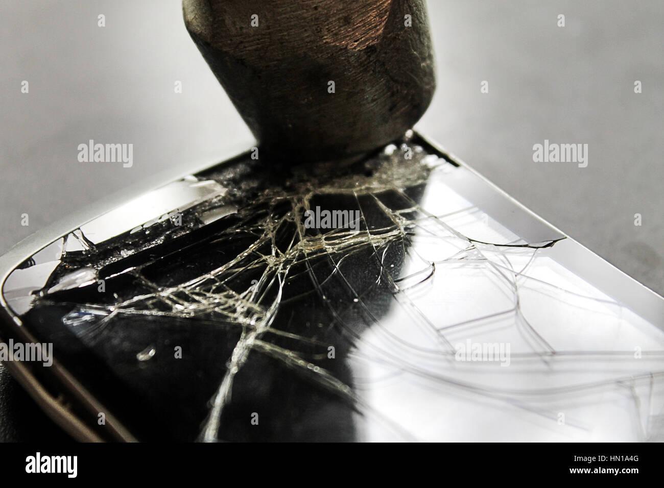 Rotto lo schermo del telefono e un martello su sfondo,un colpo di martello per il telefono cellulare, in una rabbia, Immagini Stock