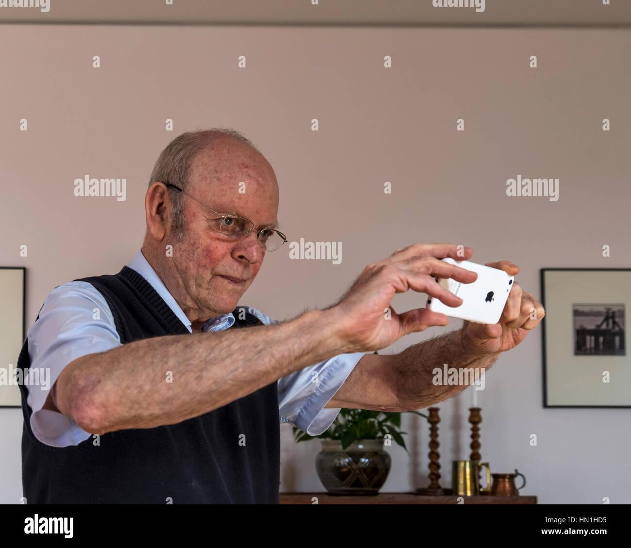 Senior anziano uomo prendendo fotografie con i-telefono cellulare Immagini Stock