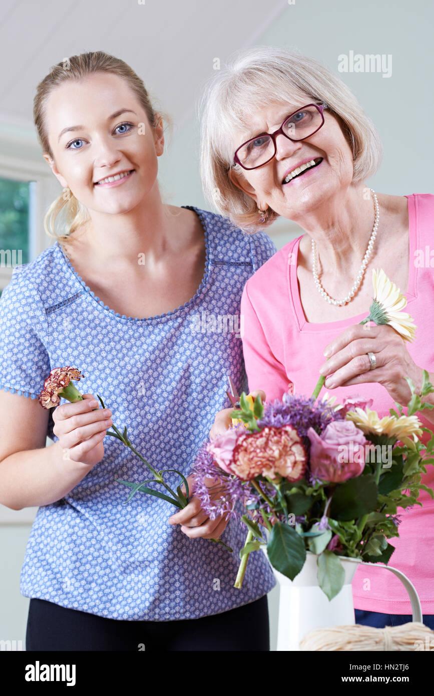 Senior donna con insegnante nella composizione floreale di classe Immagini Stock