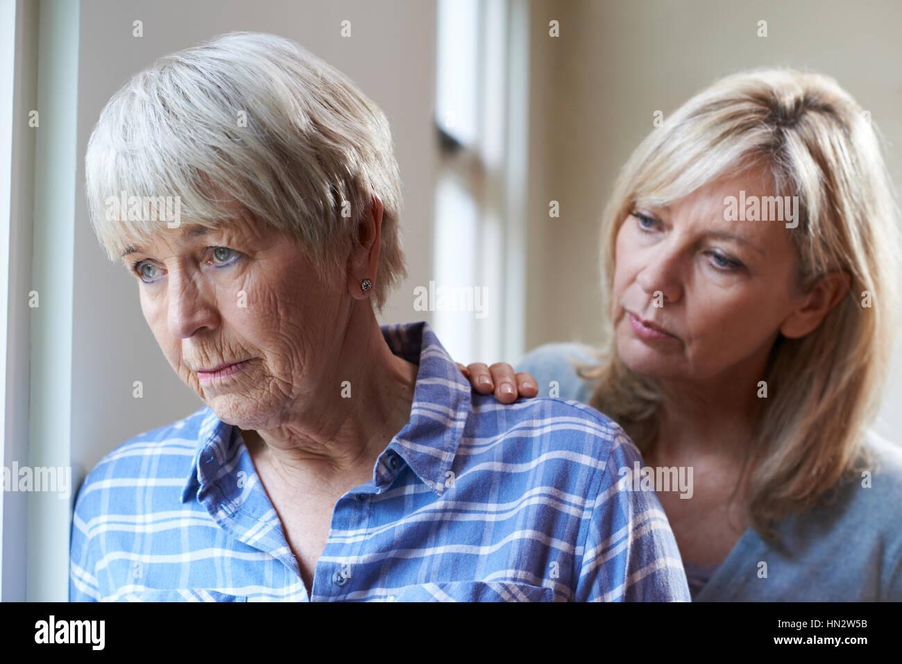Grave donna Senior con la figlia adulta a casa Immagini Stock