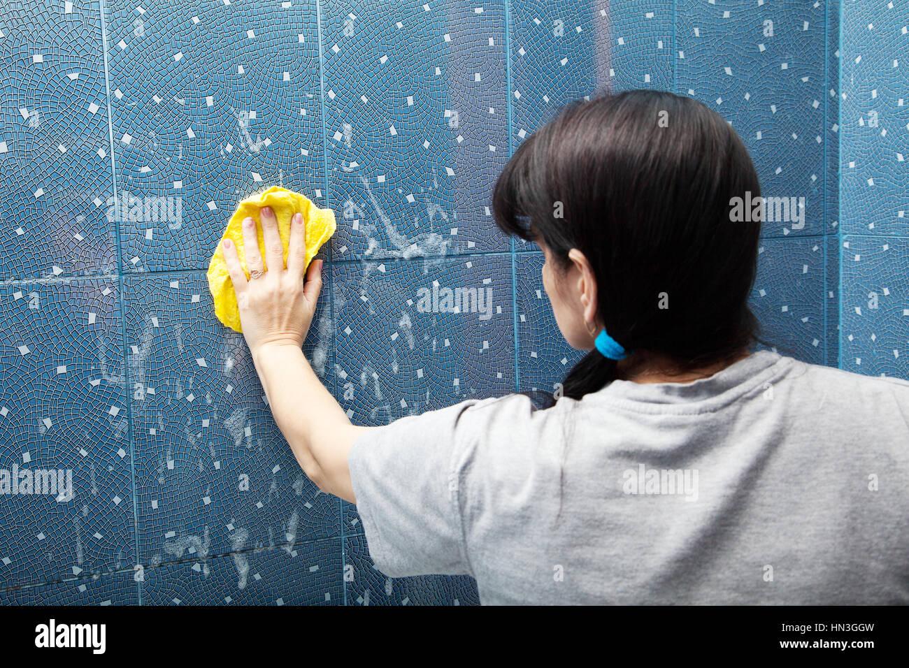 La donna in grigio di una camicia blu di lavaggio piastrelle con un