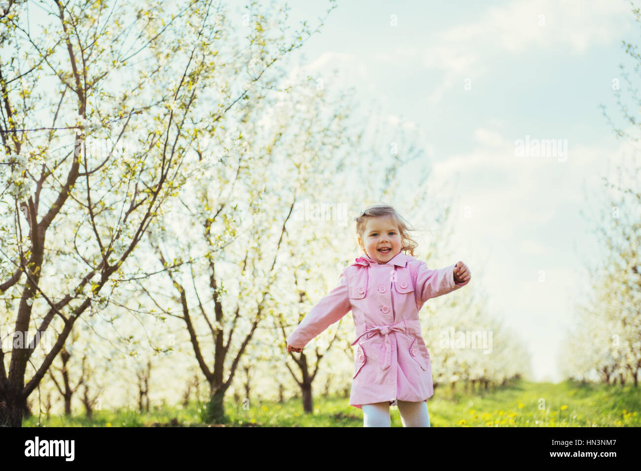 Bambino in esecuzione all'esterno alberi in fiore. Elaborazione Art e ritocco Immagini Stock