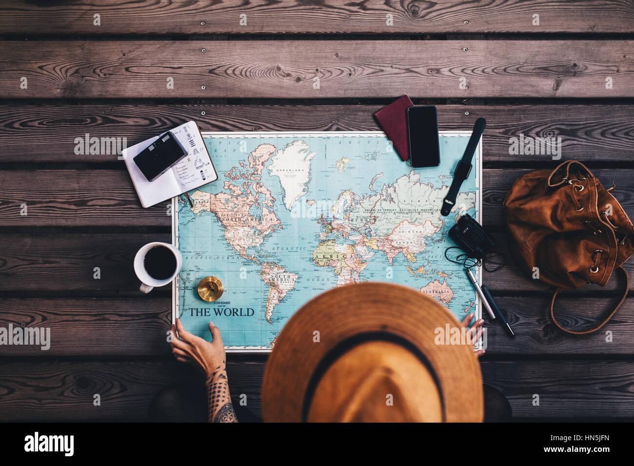 Giovane donna vacanza di pianificazione utilizzando la mappa del mondo e bussola insieme con altri accessori da Foto Stock