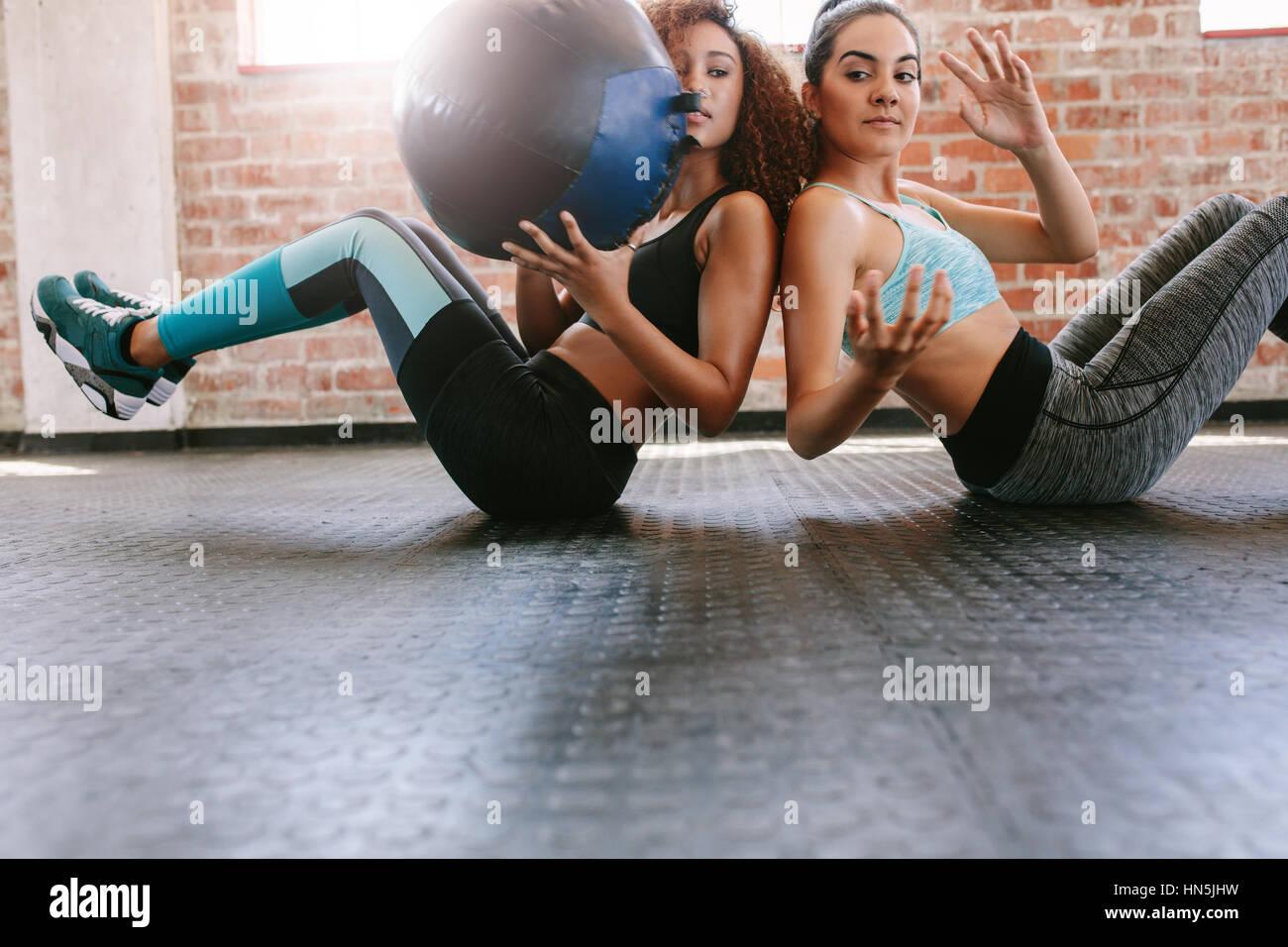 Due donne sportivo formazione con palla medica in palestra. Ragazze che lavorano fuori per modellare il loro corpo. Immagini Stock