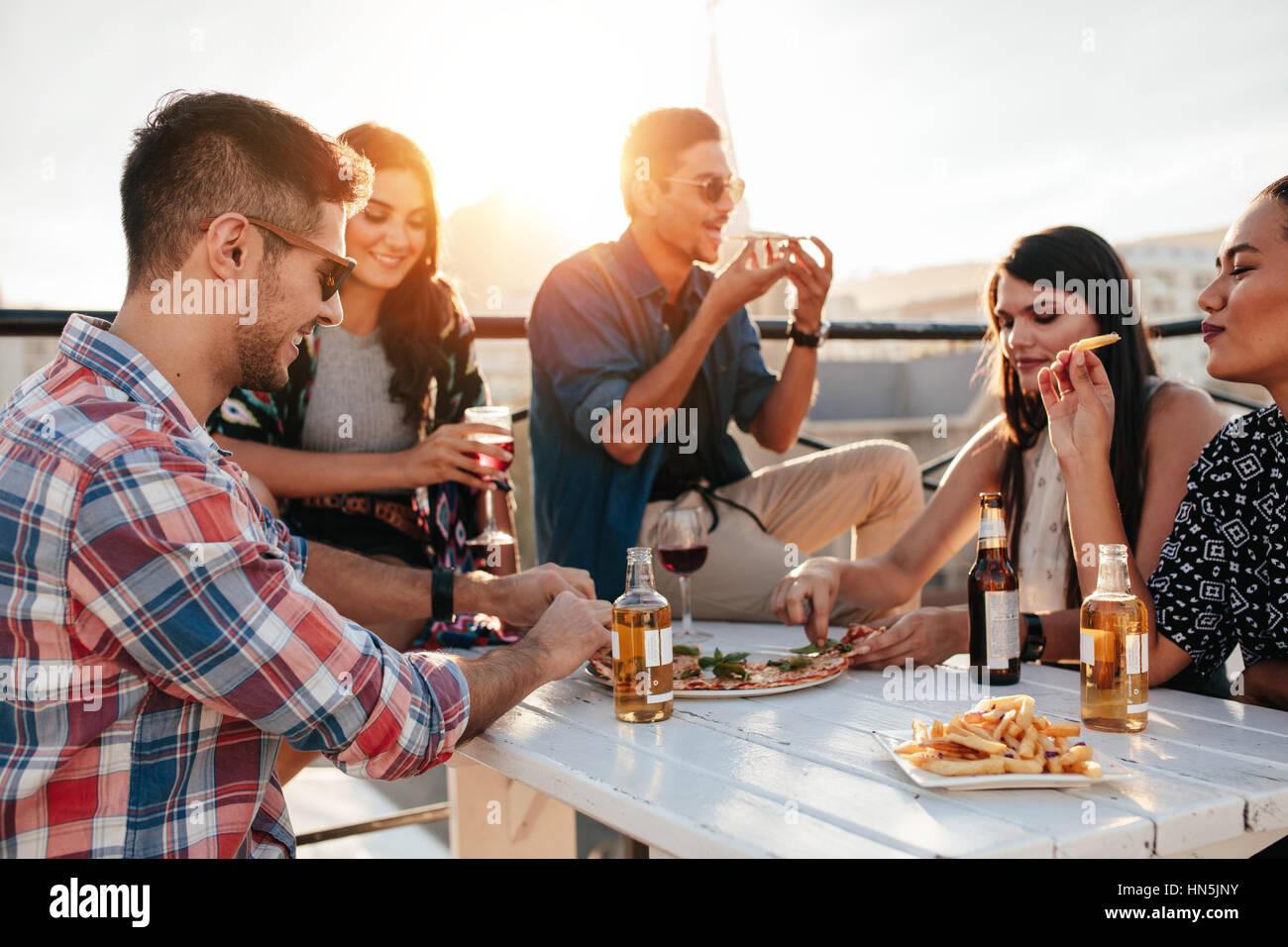 Un gruppo di giovani seduti intorno e mangiare la pizza. Amici partying e mangiare la pizza. Immagini Stock