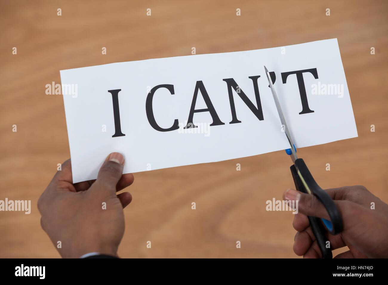 Immagine concettuale di imprenditore il taglio di un foglio di carta che legge ci cant su sfondo bianco Immagini Stock
