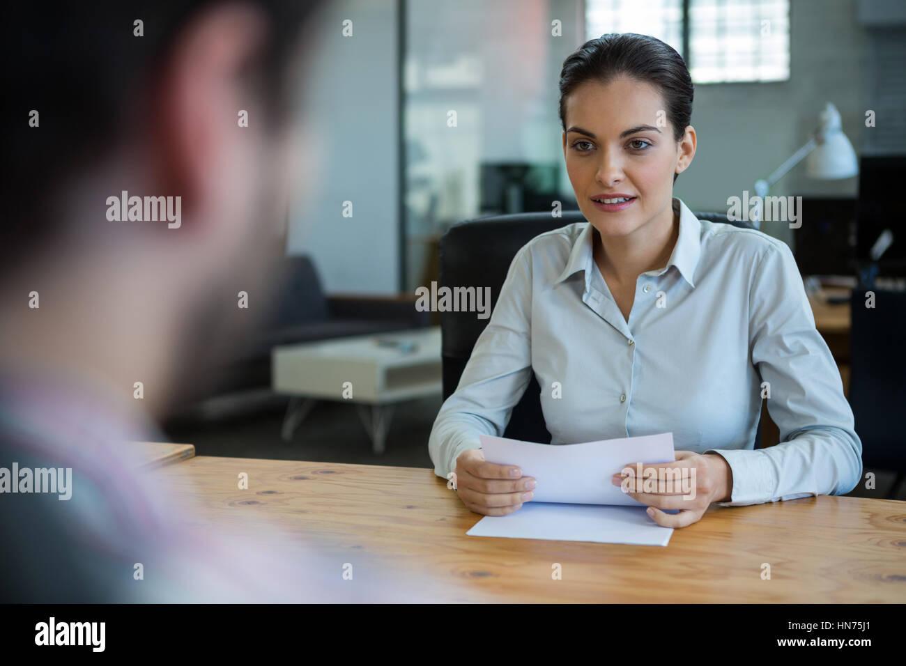 Business executive condurre il colloquio di lavoro con l'uomo in ufficio Immagini Stock