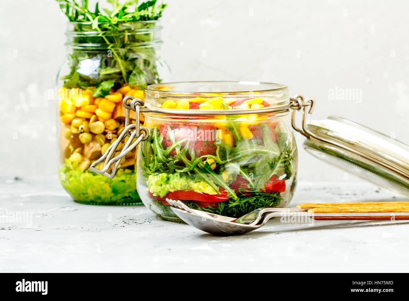 Un sano take-away a pranzo i vasetti. Guacamole, mais, tofu, fagioli, foglie di rucola. La paprica, falafel, aneto Immagini Stock