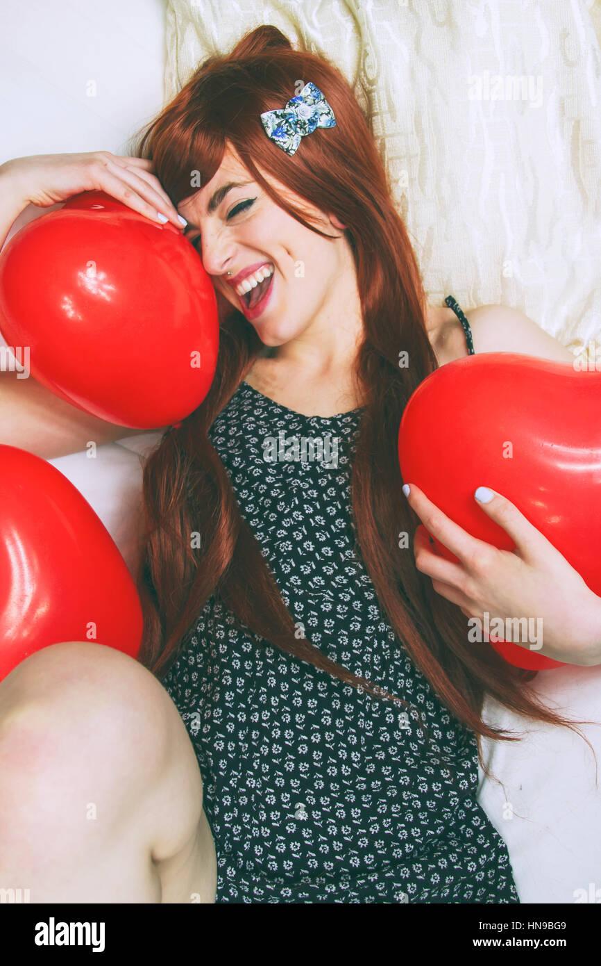 Allegro giovane donna rosso con palloncini sagomati Immagini Stock