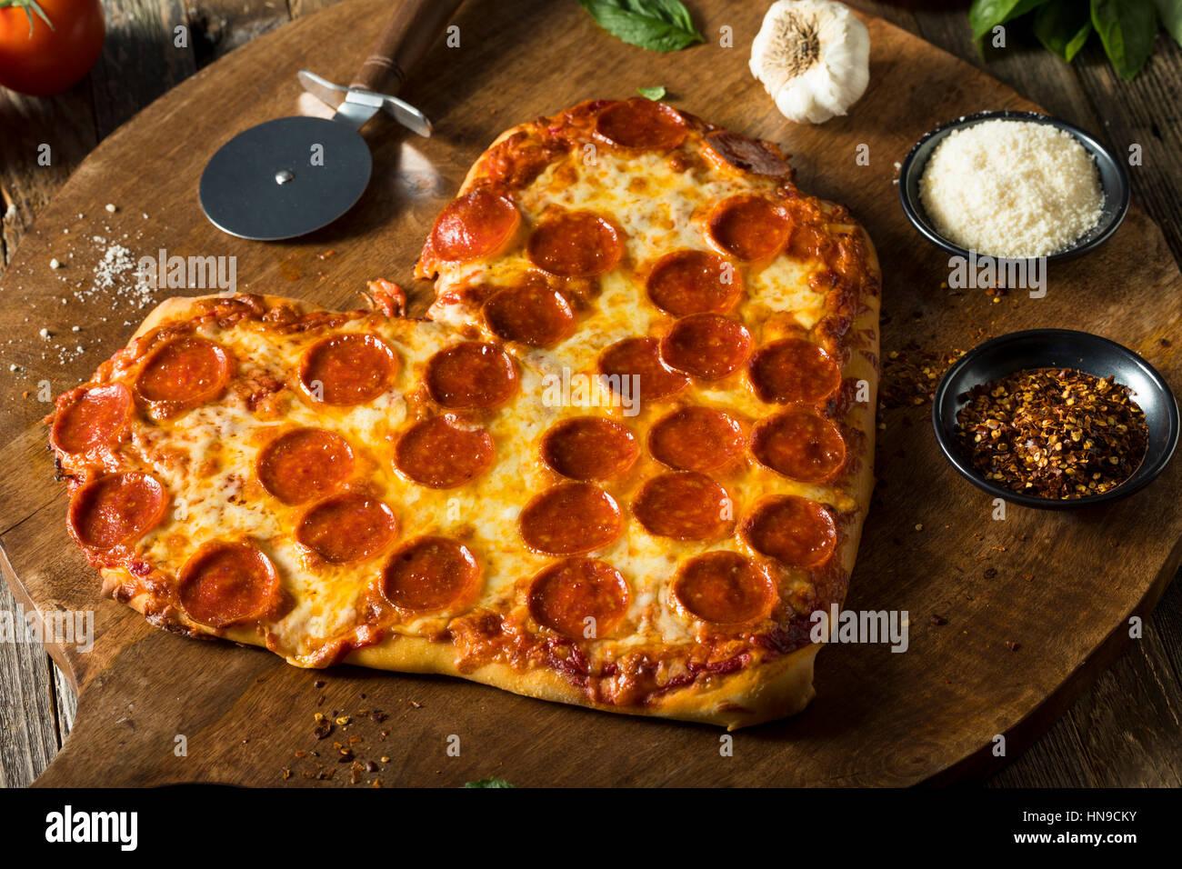 In casa a forma di cuore ad salsiccia per pizza pizza pronta da mangiare Immagini Stock