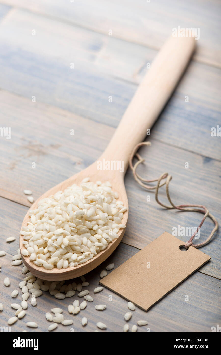 Cumulo di riso in bianco in cucchiaio di legno sul tavolo con etichetta di testo. Immagini Stock