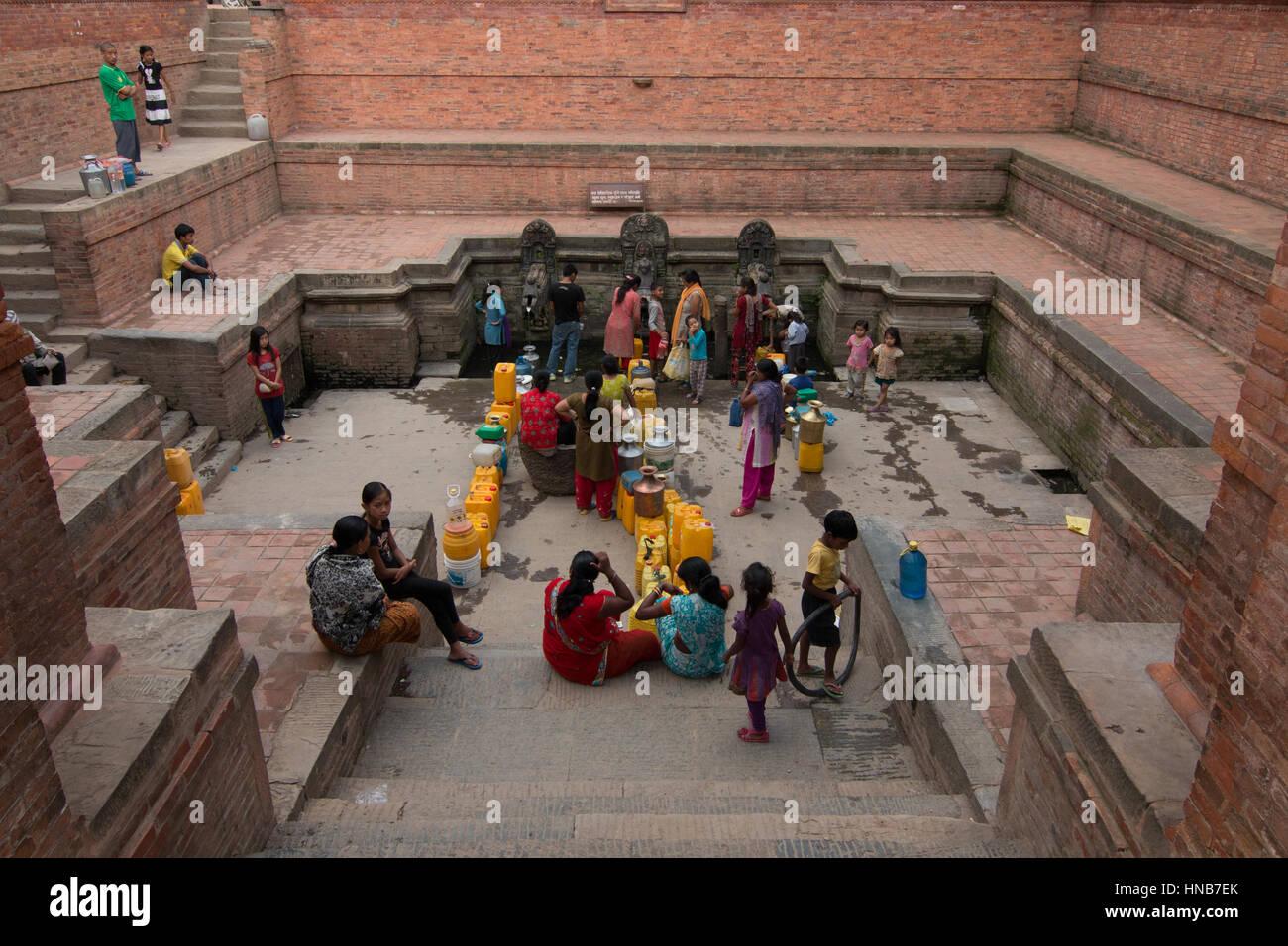 Le donne in coda per acqua dalle intricate sculture di bronzo erogatori di acqua in una pubblica piazza a Kathmandu Immagini Stock