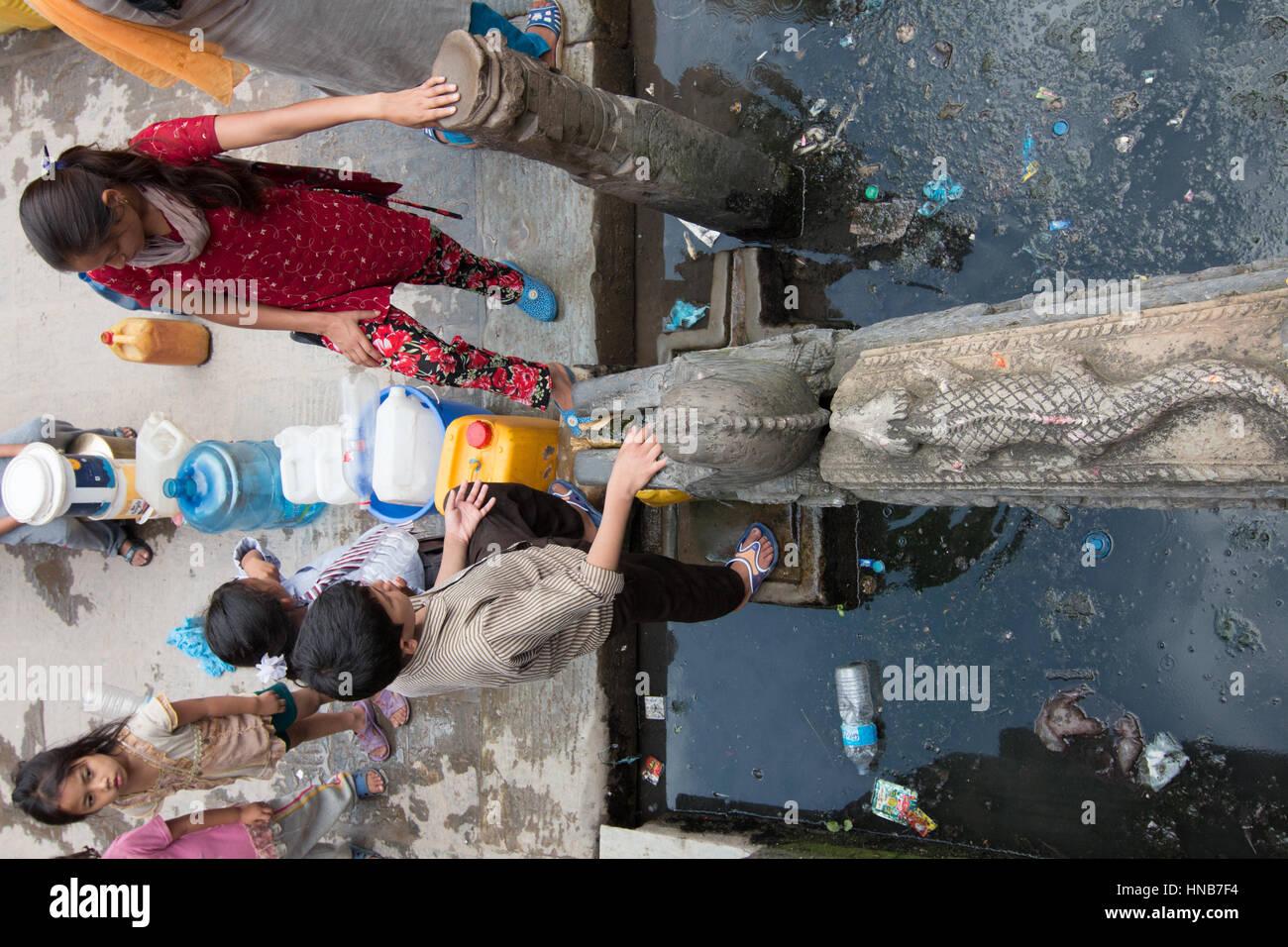 Le ragazze di raccogliere acqua in Kathmandu, Nepal, dal bronzo acqua beccucci in una pubblica piazza che proviene Immagini Stock