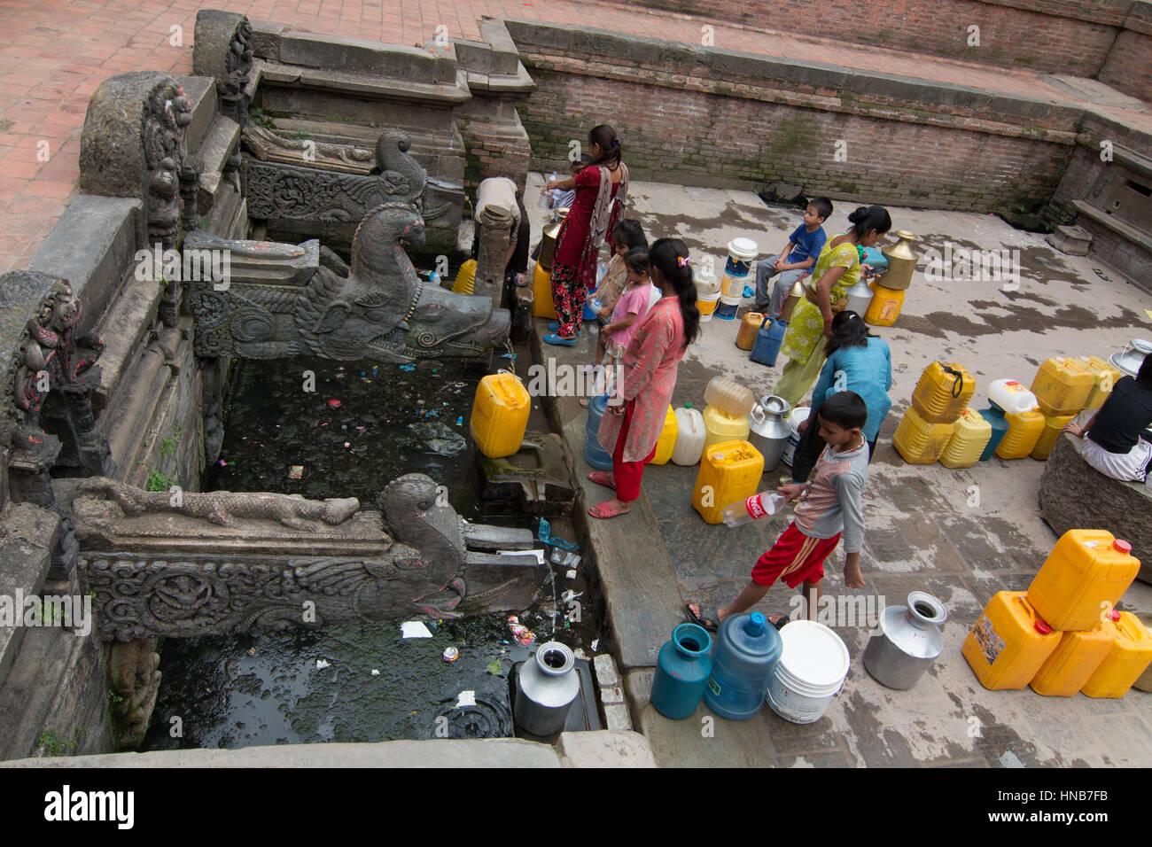 La gente in coda per acqua che proviene da sorgenti sotterranee dalle intricate sculture di bronzo beccucci in una Immagini Stock