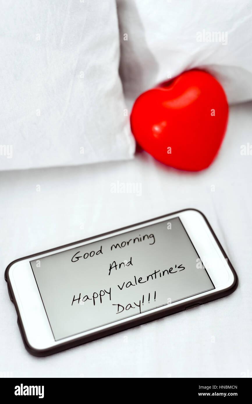 Uno smartphone, con il testo buongiorno e felice il giorno di San Valentino nel suo schermo e un cuore rosso posto Immagini Stock