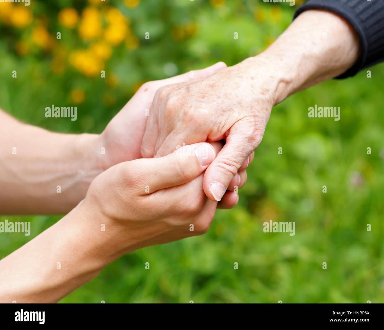 Medico la mano che regge un rugosa mano anziani Immagini Stock