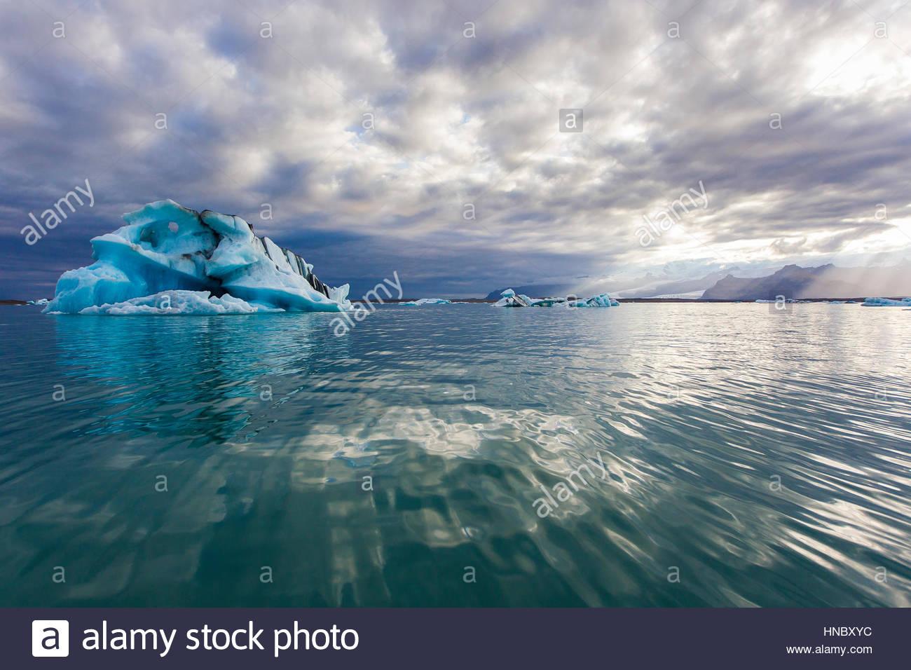 Nuvole fly overhead e ondulazioni di acqua circondano un grande Iceberg di Jokulsarlon laguna glaciale. Immagini Stock
