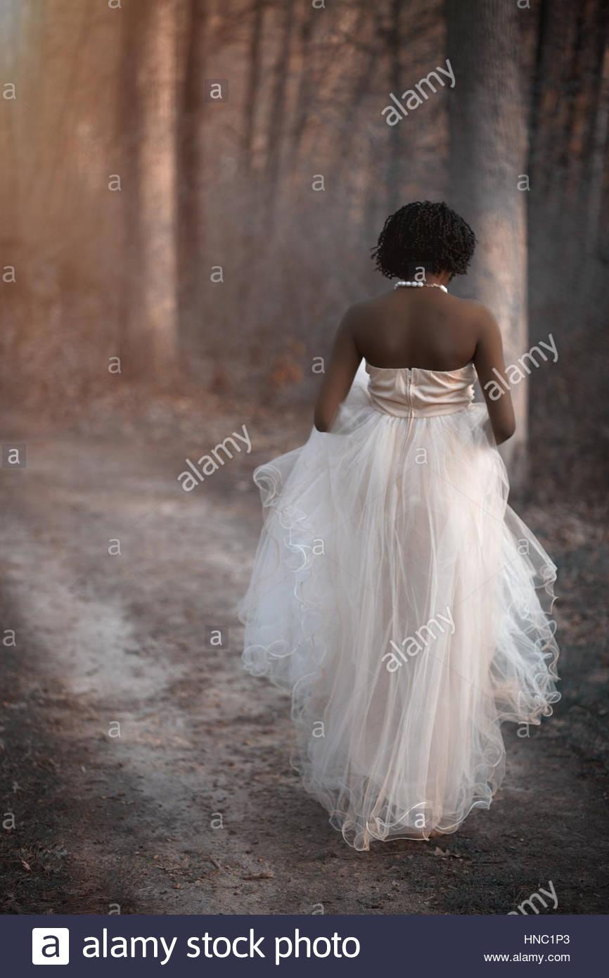 Elegante giovane donna nel bosco a piedi Immagini Stock