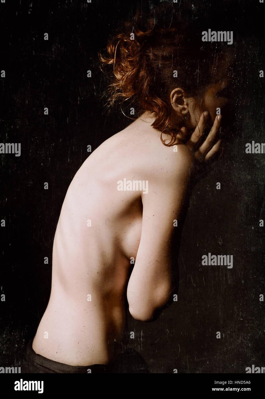 Malinconico ritratto di una giovane donna tra il buio. Grunge effetto texture Immagini Stock