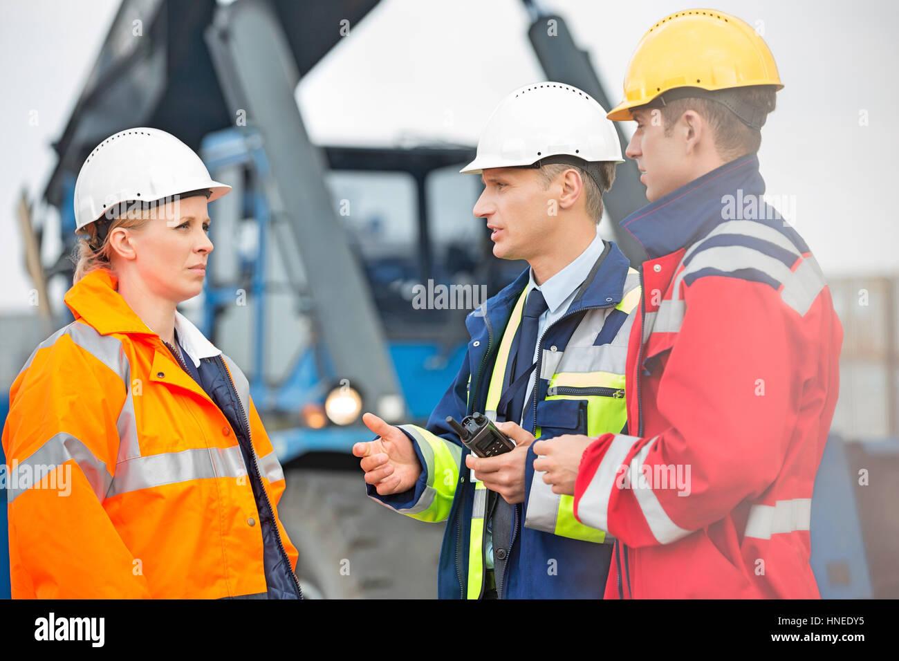 I lavoratori di discutere in cantiere di spedizione Immagini Stock