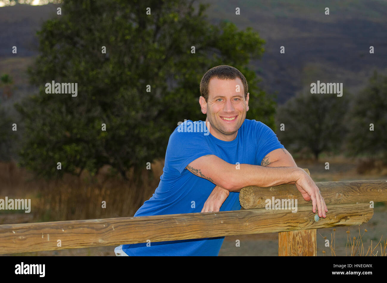 Uomo sorridente appoggiato su di una recinzione di legno godendo la vita all'aperto Immagini Stock