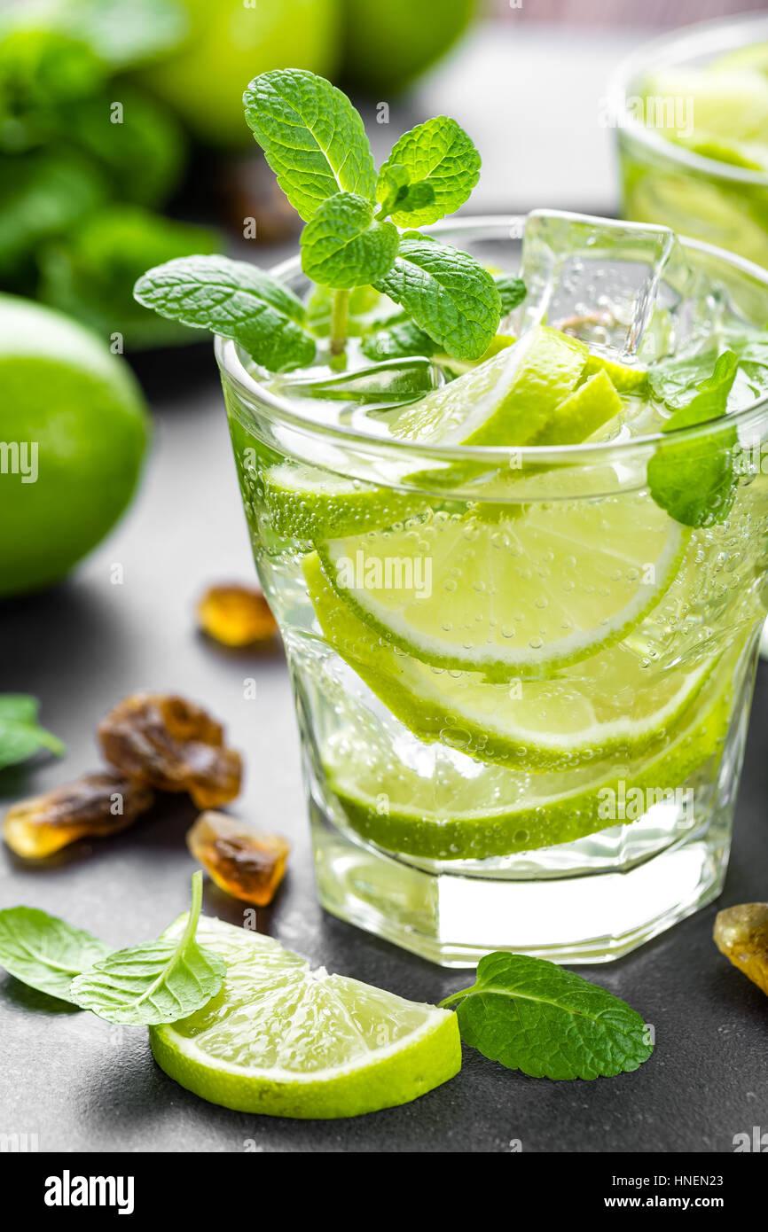 Estate menta lime rinfrescante cocktail mojito con il rum e il ghiaccio in vetro su sfondo nero in vista superiore Immagini Stock