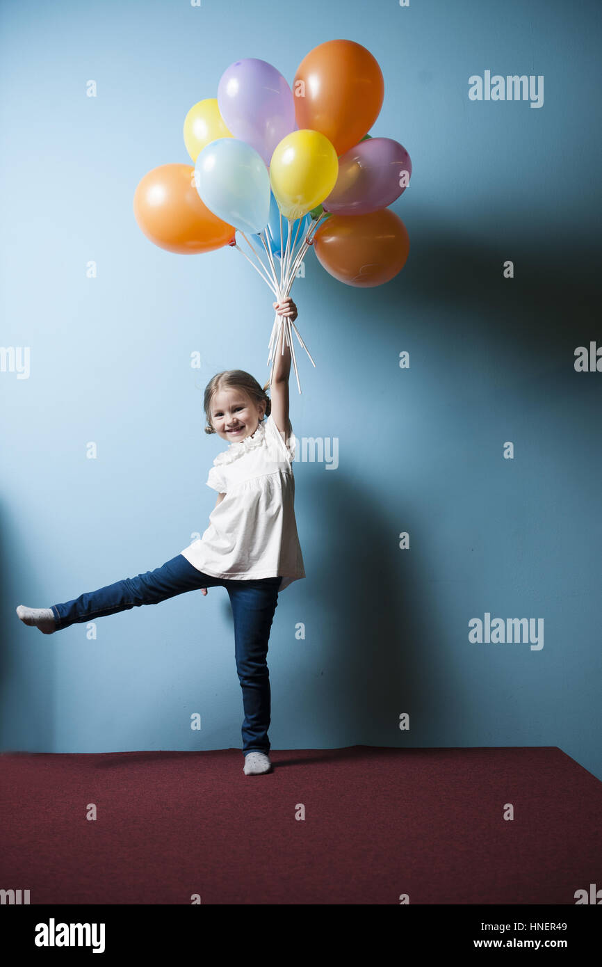 Giovane ragazza fingendo di essere sollevato dal grappolo di palloncini Immagini Stock