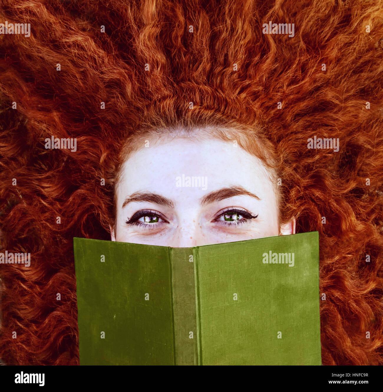 Giovane donna redhead la lettura di un libro Immagini Stock