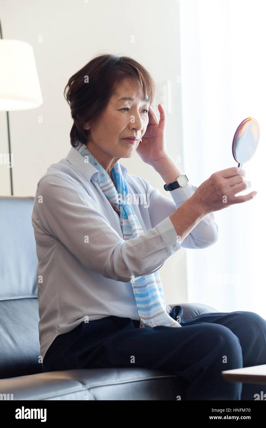 Un senior donna vedendo una mano specchio Immagini Stock
