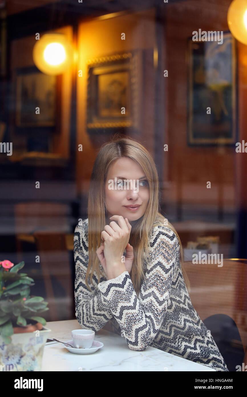 La donna in attesa all'interno di una elegante caffetteria. Uno stile di vita urbano Immagini Stock