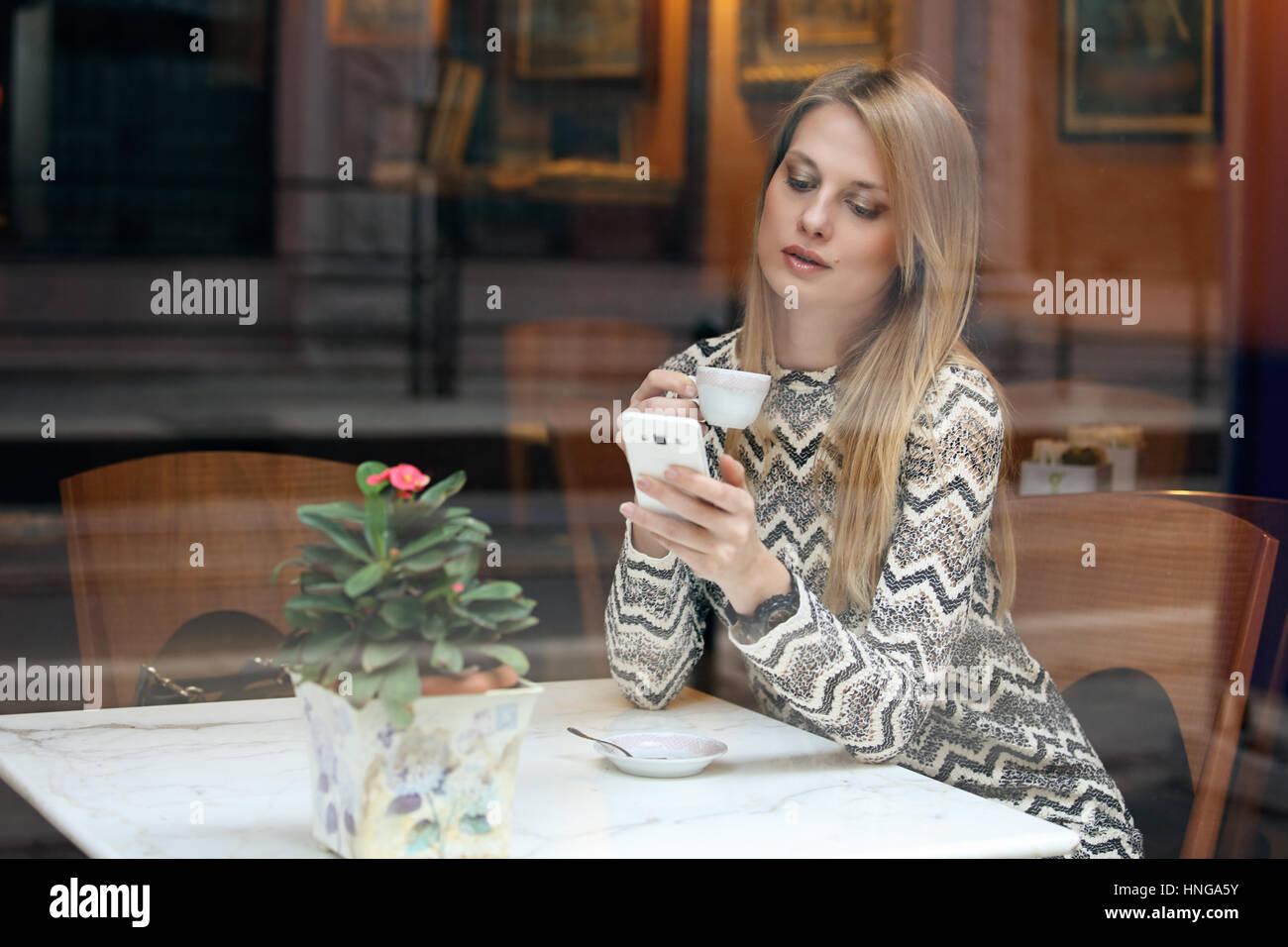 Bella ragazza utilizzando il suo telefono cellulare in cafe. Lo stile di vita della città Immagini Stock