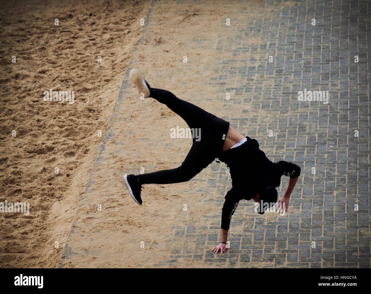Un uomo in nero practice parkour sul lungomare di Brighton Immagini Stock