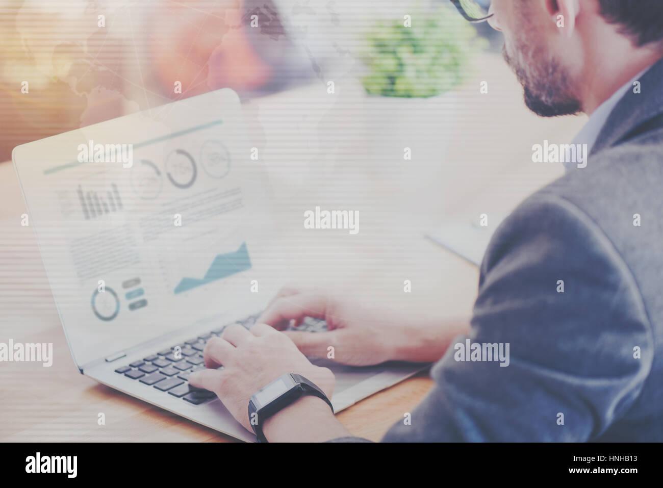 Piacevole uomo coinvolto workign sul laptop Immagini Stock