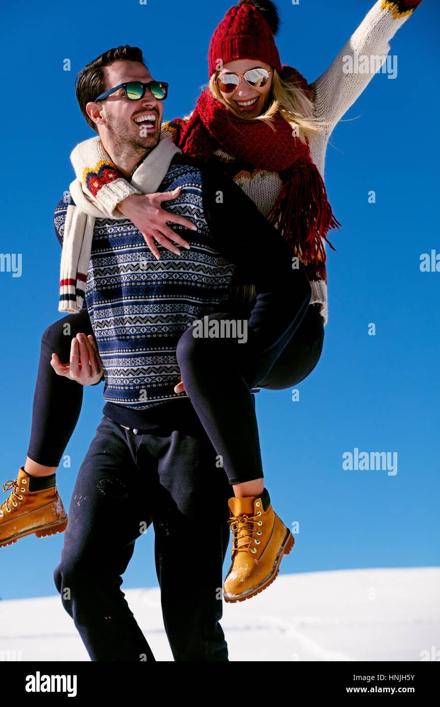Giovane giocare nella neve. Uomo Donna dando piggyback ride per le vacanze invernali. Immagini Stock
