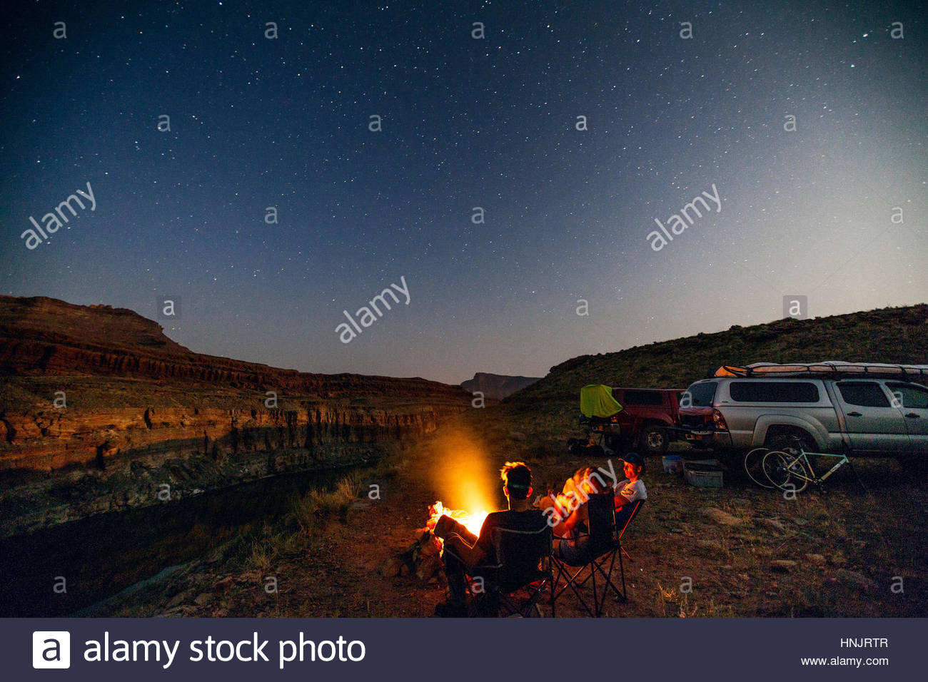 Persone campeggio sotto le stelle sulle rive di un fiume. Immagini Stock