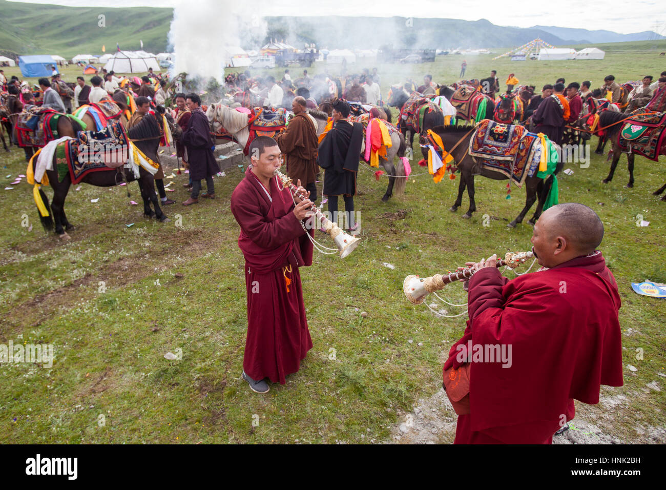 Monaci buddisti tibetani riprodurre strumenti tradizionali di benedire i piloti del Cavallino prima racing al Manigango Immagini Stock