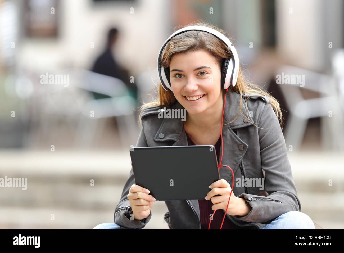 In Panchina Con Le Cuffie   Bella ragazza ascolto di musica con cuffie e  tablet guardando 369141506a32