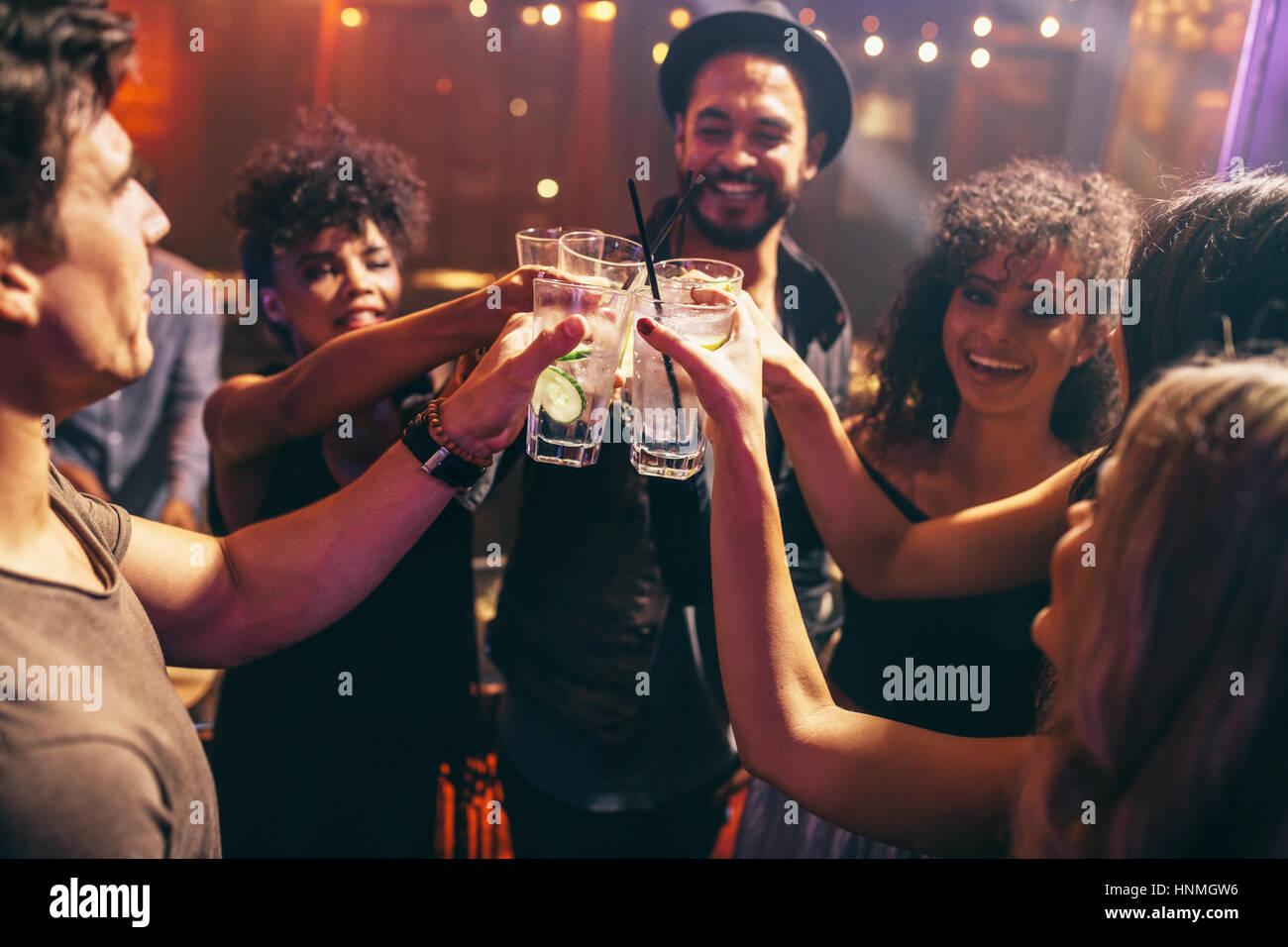 Gruppo di amici avente le bevande presso il night club party. I giovani godono presso un bar cocktail di tostatura. Foto Stock