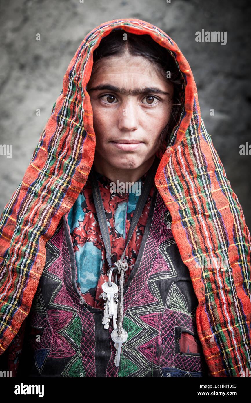 Afghanistan, Wakhan corridor, un ritratto di una donna con abiti colorati e velo, legato sopracciglio e attraversato Immagini Stock
