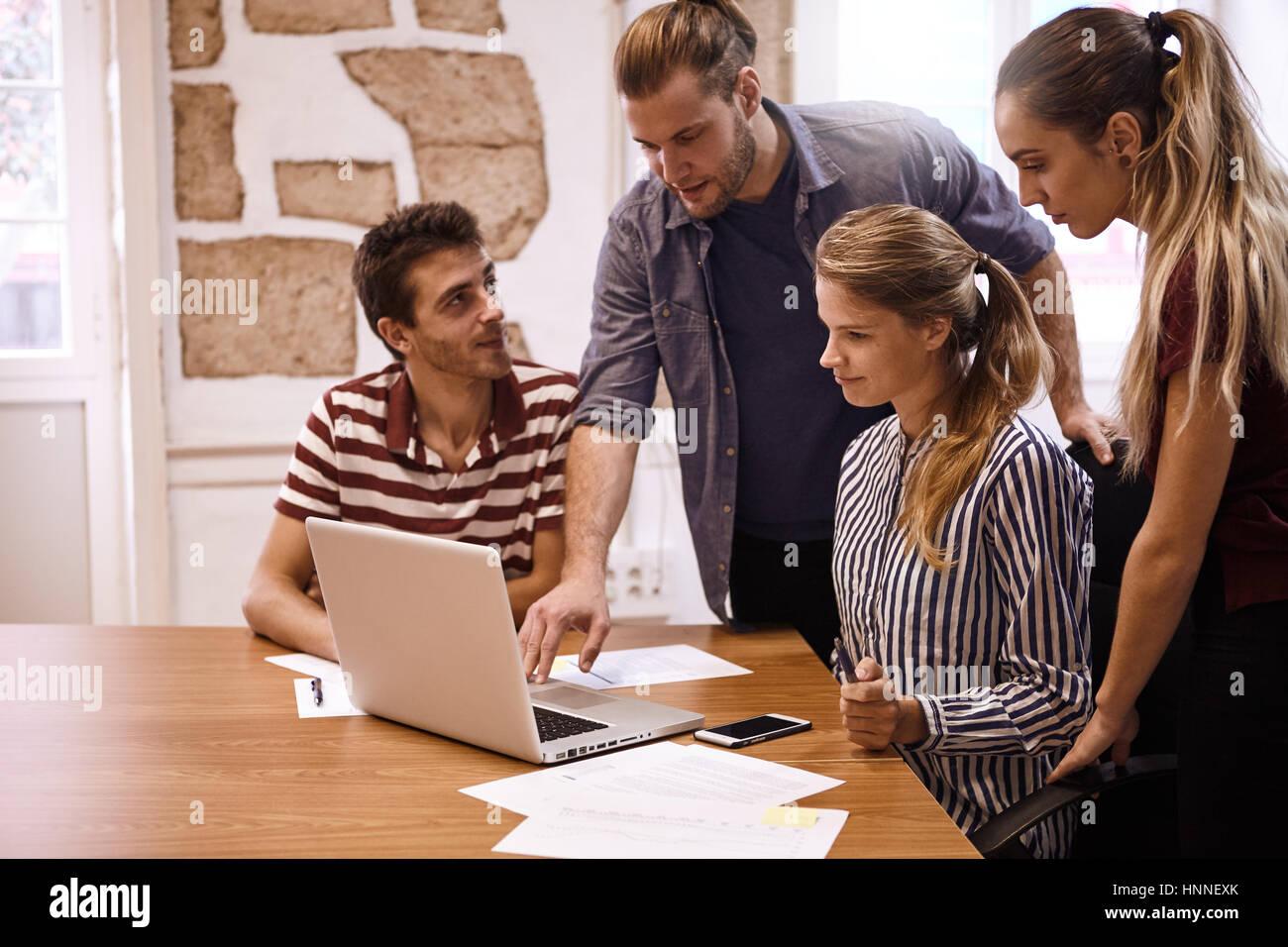 Young business team seduti e in piedi intorno a un computer portatile mentre un maschio è la realizzazione Immagini Stock